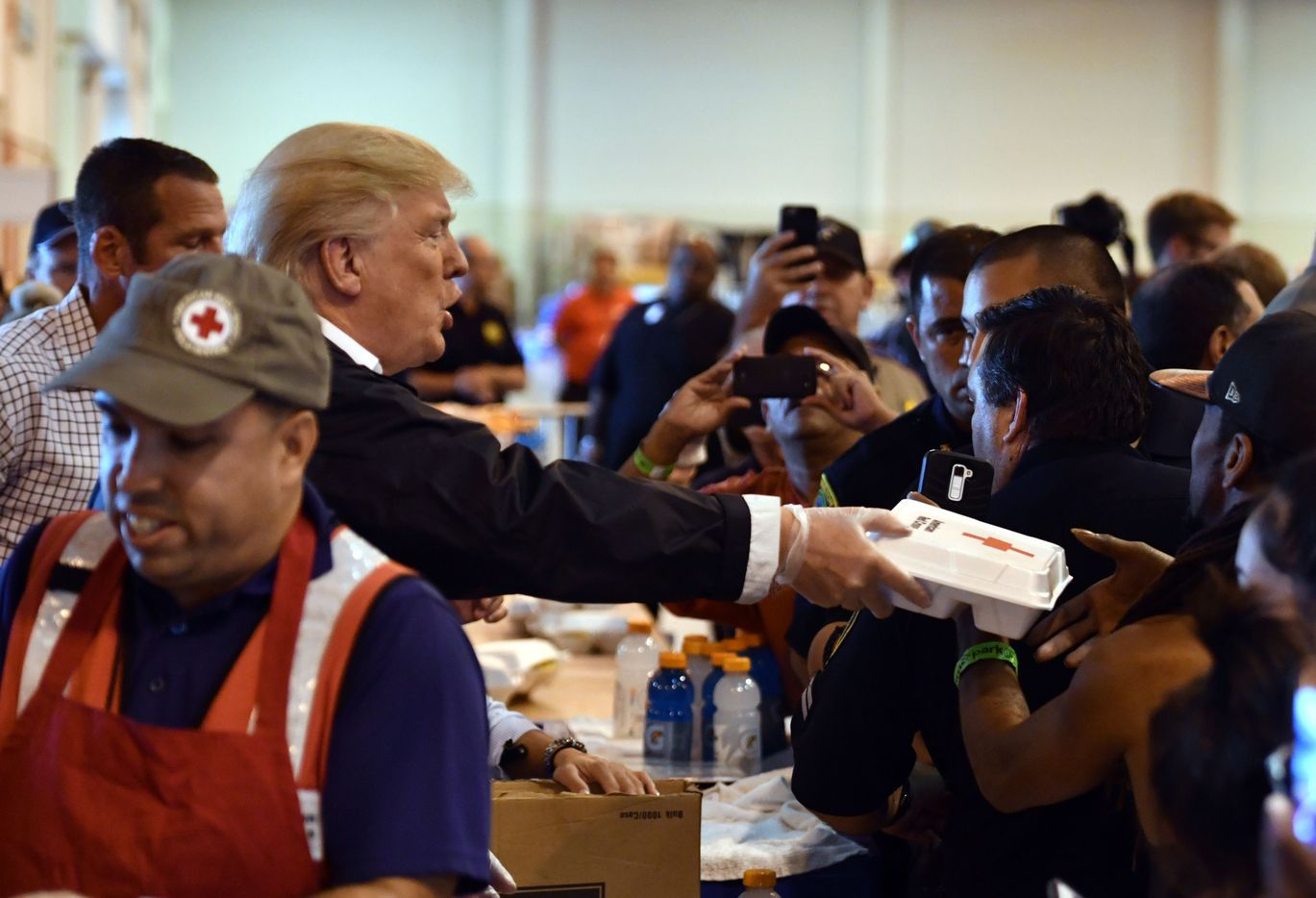 President Donald Trump serves food to Hurricane Harvey victims at NRG Center in Houston on Saturday.
