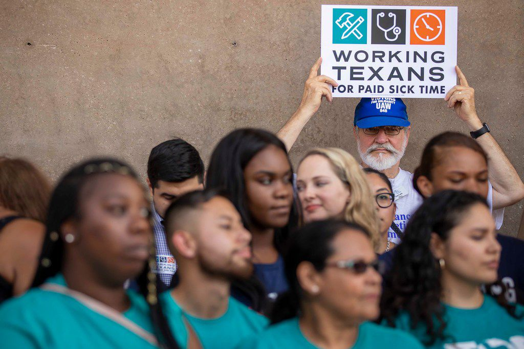 Gene Lantz of the Texas Alliance for Retired Americans holds a sign during a press conference before a coalition of labor and faith groups and political activists delivered petitions to at City Hall calling for a city ordinance mandating paid sick time to be placed on the November ballot on June 11, 2018, in Dallas.
