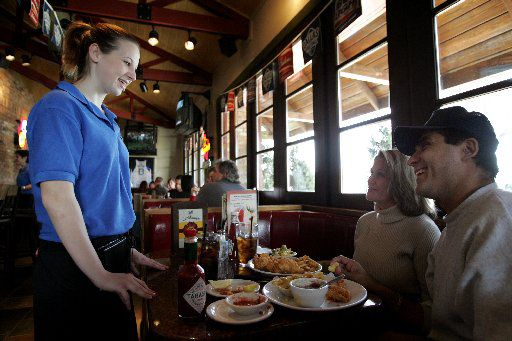 Cassandra Hayes (L) talks with some of her customers Rudy Moreno (R), of Garland, and Pauline Chaney (middle), of Mesquite, while waiting tables at Cheddar's in Dallas on a Saturday afternoon