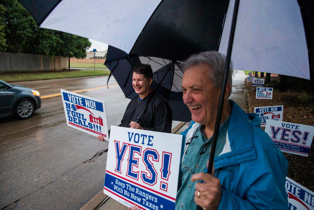 Jeff Rutledge (left), who's voting against a new stadium for the Texas Rangers, and Dave Schwarte, who's voting for the stadium, held opposing signs outside a polling place Tuesday at the North East Branch of the Arlington Public Library on Brown Boulevard. They said they disagree on the issue, but both love the Rangers. (Ashley Landis/Staff Photographer)