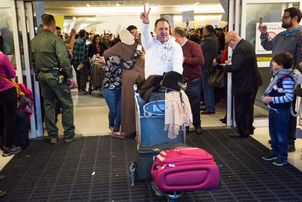 Motasim Abusaad of Irving celebrates as he wheels the baggage of his sister Nancy Abusaad and niece Zenna Jarrar out of the airport after they arrived from Jordan at DFW International Airport on Sunday, Jan. 29, 2017.  (Smiley N. Pool/The Dallas Morning News)