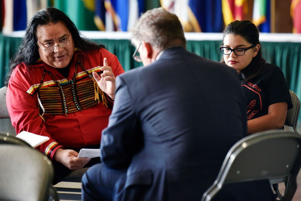 Leroy Peña, a legislative aide with the Lipan Apache Tribe of Texas, left, and Angela Andrade, right, a supporter of Indigenous Peoples' Day, speak to Dallas City Council member David Blewett about the word usage in a document declaring the second Monday in October as Indigenous People's Day at Dallas City Hall on Tuesday. Blewett was opposed to approving such a resolution because of certain words in the resolution that he felt should be left out. Ben Torres/Special Contributor