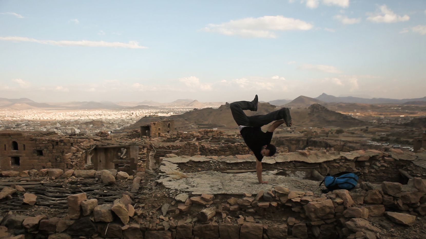 "A dancer breaks amid ruins in Yemen in a scene from ""Shake the Dust,"" a documentary about the worldwide influence of break dancing"