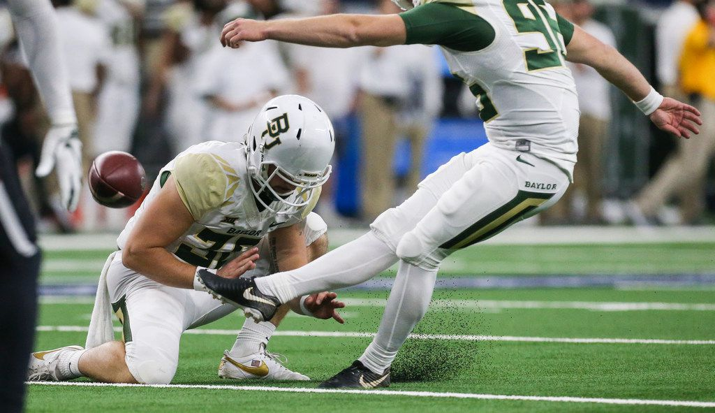 Baylor Bears place kicker Connor Martin (96) kicks the ball from punter Drew Galitz (36) to score the extra point during the second half of a matchup between Baylor and Texas Tech on Saturday, Nov. 24, 2018 at AT&T Stadium in Arlington, Texas. (Ryan Michalesko/The Dallas Morning News)