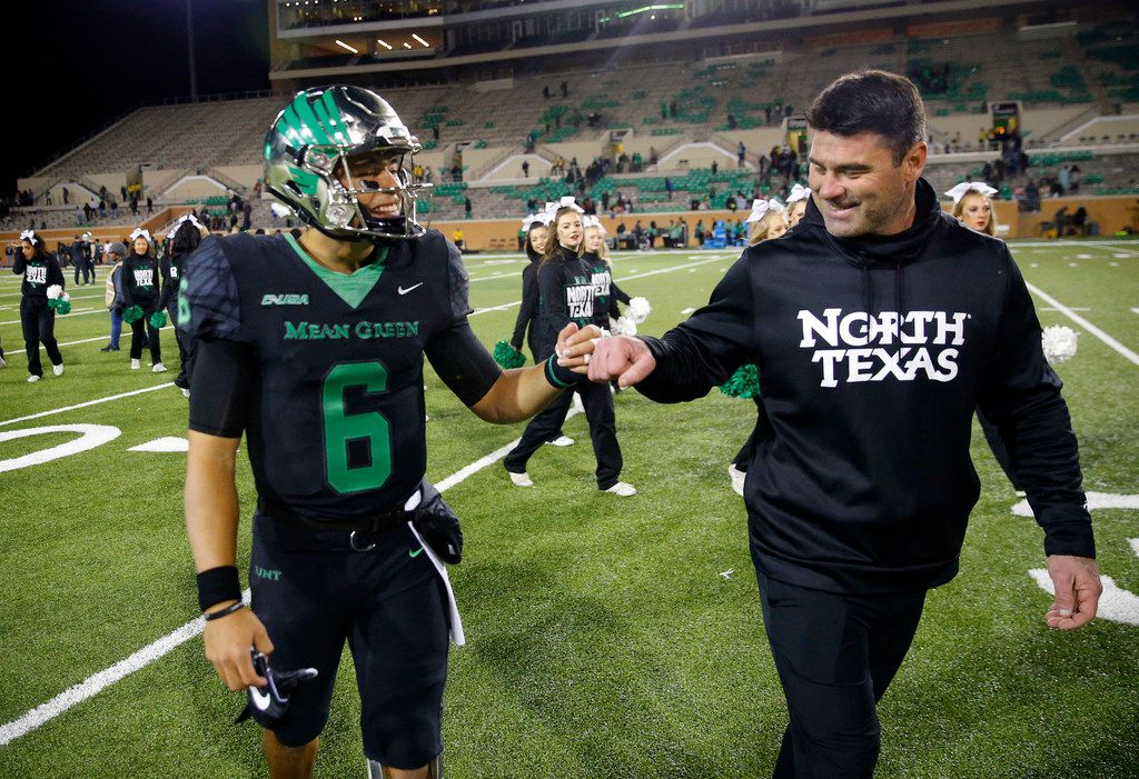 FILE - North Texas Mean Green head coach Seth Littrell fist bumps quarterback Mason Fine (6) on his injured hand following their win over the Florida Atlantic Owls at Apogee Stadium in Denton, Texas, Thursday, November 15, 2018. Fine left the game and got stitches in his hand following a third quarter injury. (Tom Fox/The Dallas Morning News)