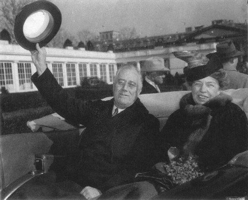 Franklin Delano Roosevelt and his wife Eleanor Roosevelt are seen in the back seat of an open limousine arriving at the White House after his inauguration in 1941.