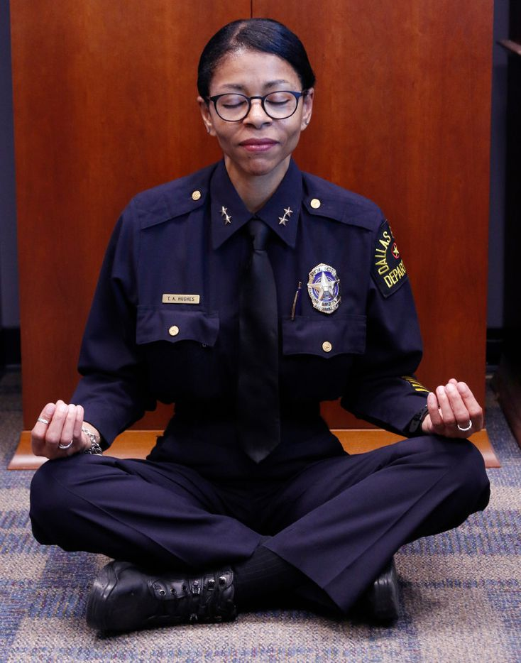 Assistant Chief Tammie Hughes demonstrates how she meditates in her office at Dallas police headquarters.