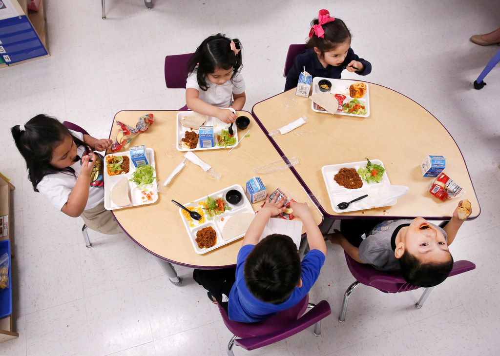 Pre-K students clockwise from left, Guillermina Pimentel, Vida De Paz, Daniela Azuara, Edwin Ventura, and Ibarra Isaias eat their taco lunch before a nap at the newly-opened Arlington Park Early Childhood Center in Dallas on March 27.