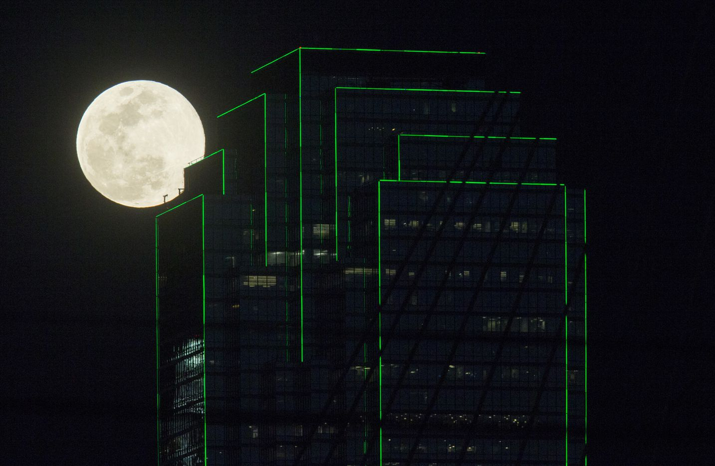 """A full """"worm"""" moon supermoon rises near the Bank of America building on March 20 in downtown Dallas."""