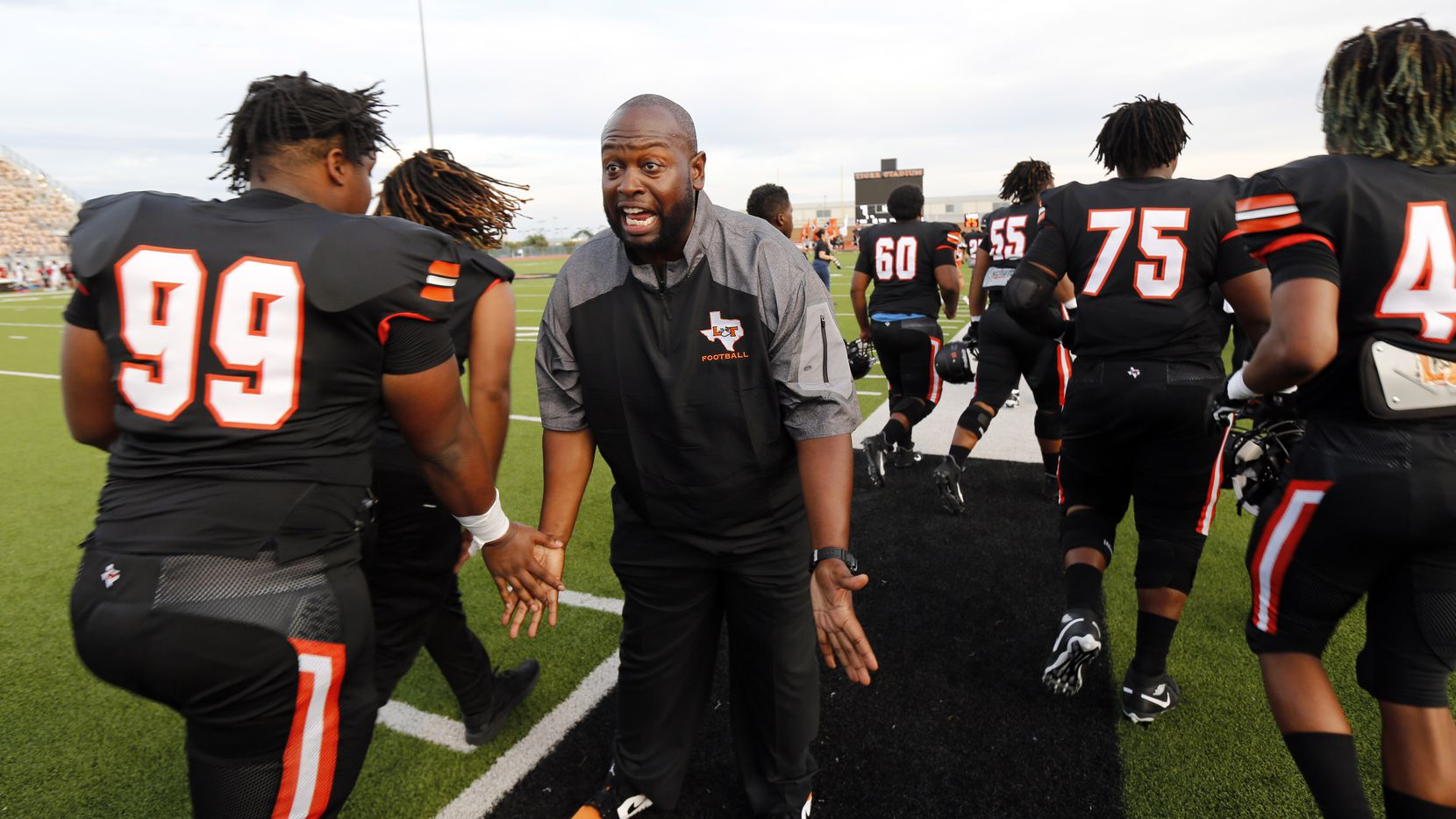 Lancaster head coach Christopher Gilbert slaps hands with his players after the team's introduction at Beverly D. Humphrey Tiger Stadium in Lancaster Texas, Friday, August 30, 2019.