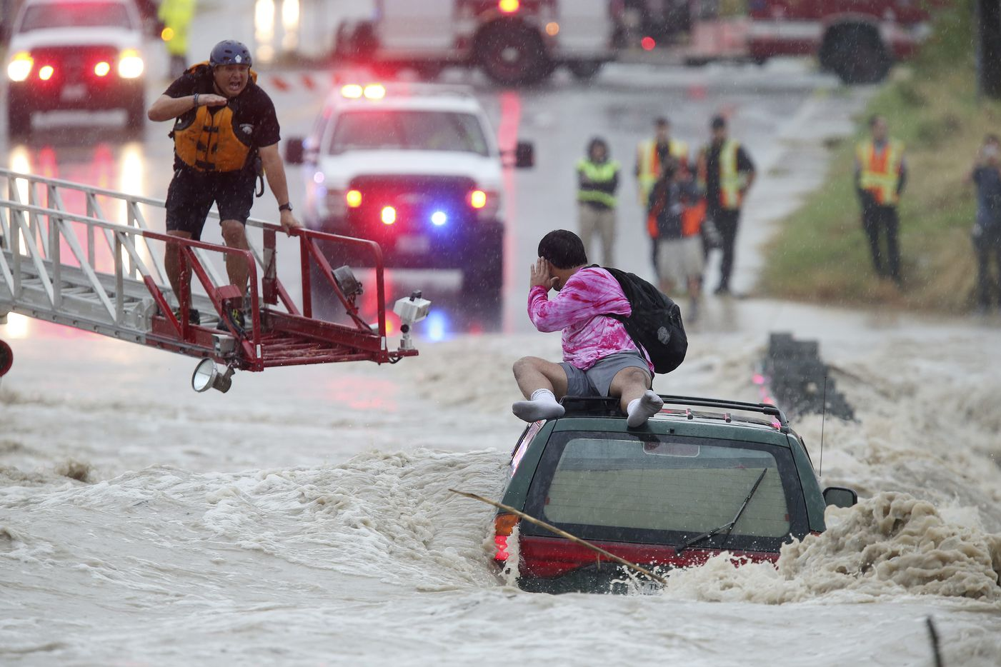 San Antonio Fire Department personnel rescued a man trapped Monday on top of his submerged vehicle at a low water crossing on Pinn Road by State Highway 151.