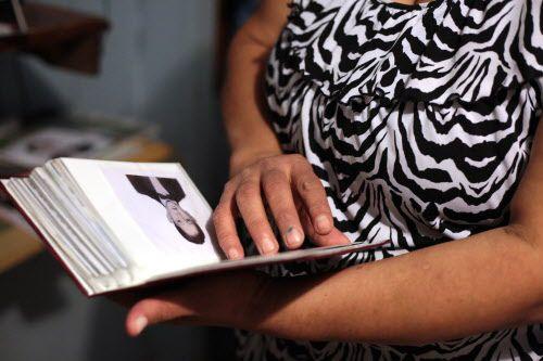 Graciela Granillo contempla un álbum de fotos de su hijo Roendy, quien falleció en el Norte de Texas por un golpe de calor. (FOTO MARÍA OLIVAS/ESPECIAL PARA AL DÍA)