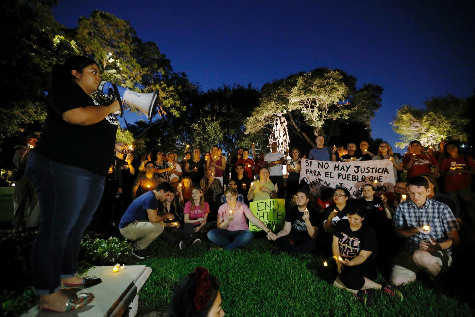 A statue of Robert E. Lee stands in the background as Democratic Socialists of America, North Texas Group, co-chair Kristian Hernandez leads a demonstration against white supremacy and holds a candlelight vigil in remembrance of Heather Heyer at Lee Park in Dallas on Aug. 23, 2017.