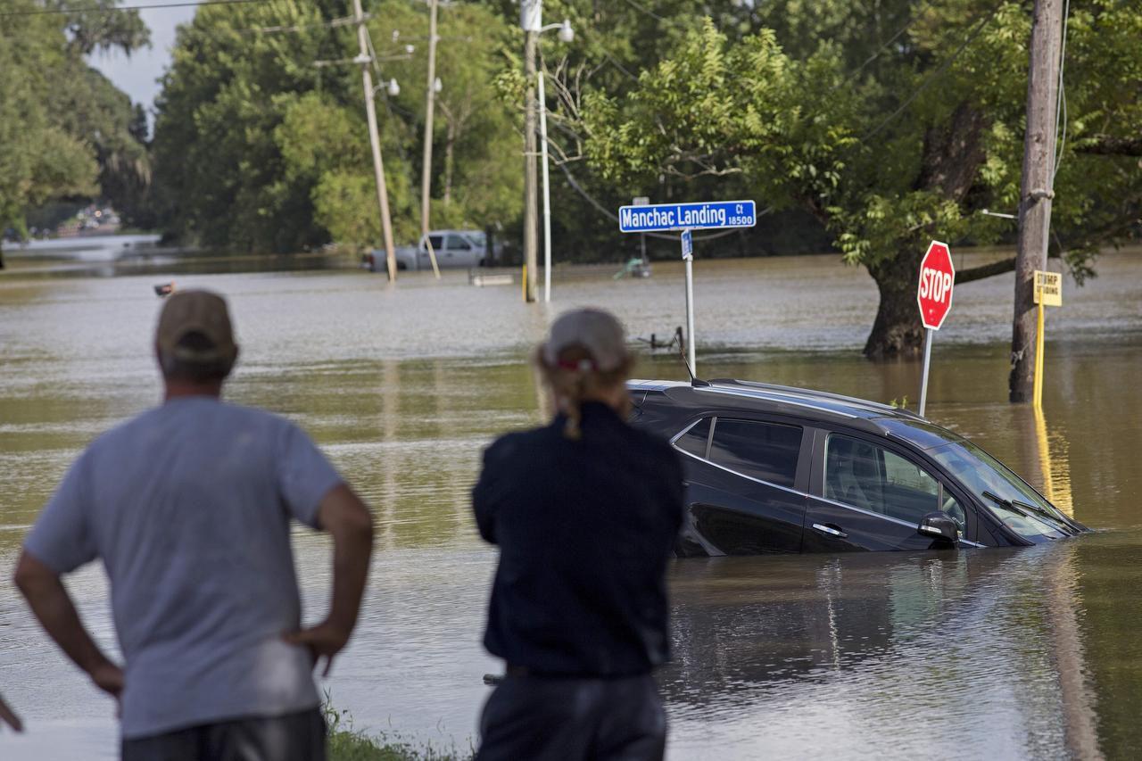Vecinos contemplan un vehículo sumergido en el agua en la carretera Old Jefferson, en Prairieville, Louisiana. (AP/MAX BECHERER)
