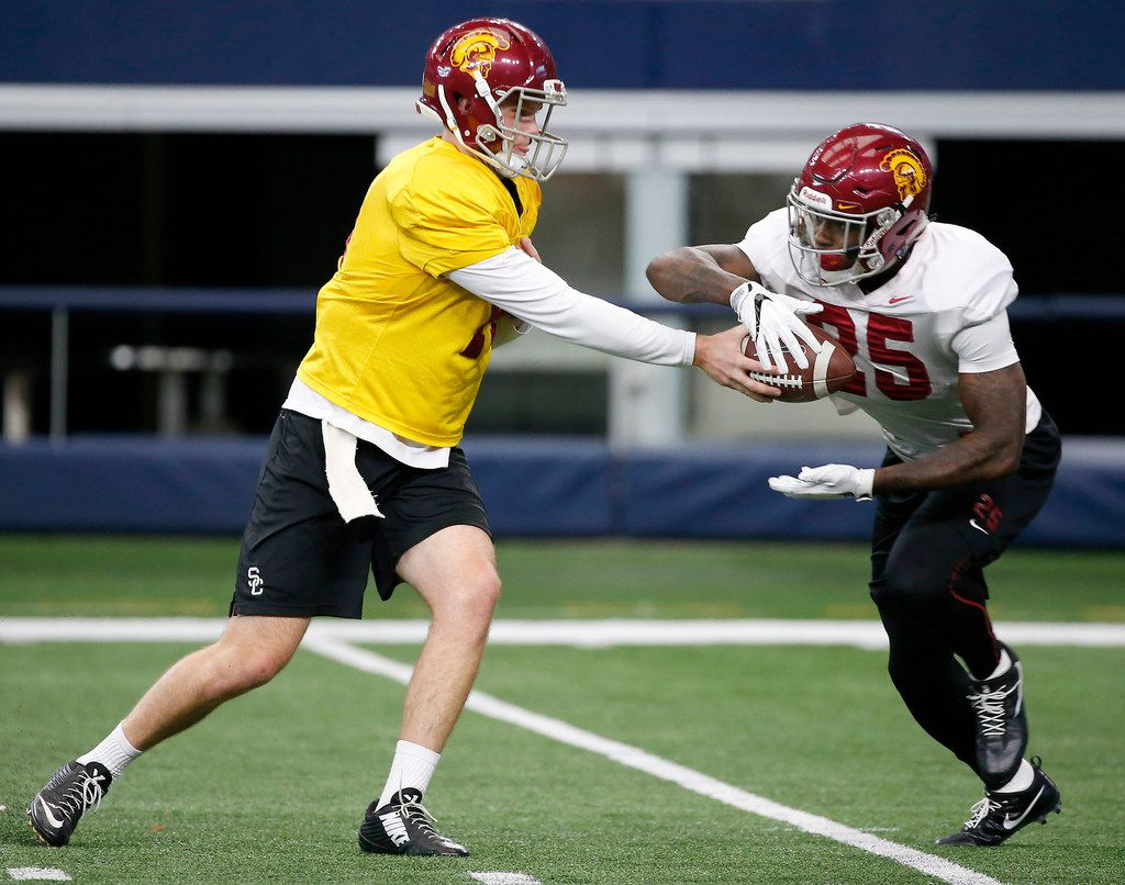 USC quarterback Sam Darnold (left) hands the ball to running back Ronald Jones II during practice at AT&T Stadium in Arlington, Texas, Monday, Dec. 25, 2017. USC will play Ohio State in Cotton Bowl on Dec. 29. (Jae S. Lee/The Dallas Morning News)