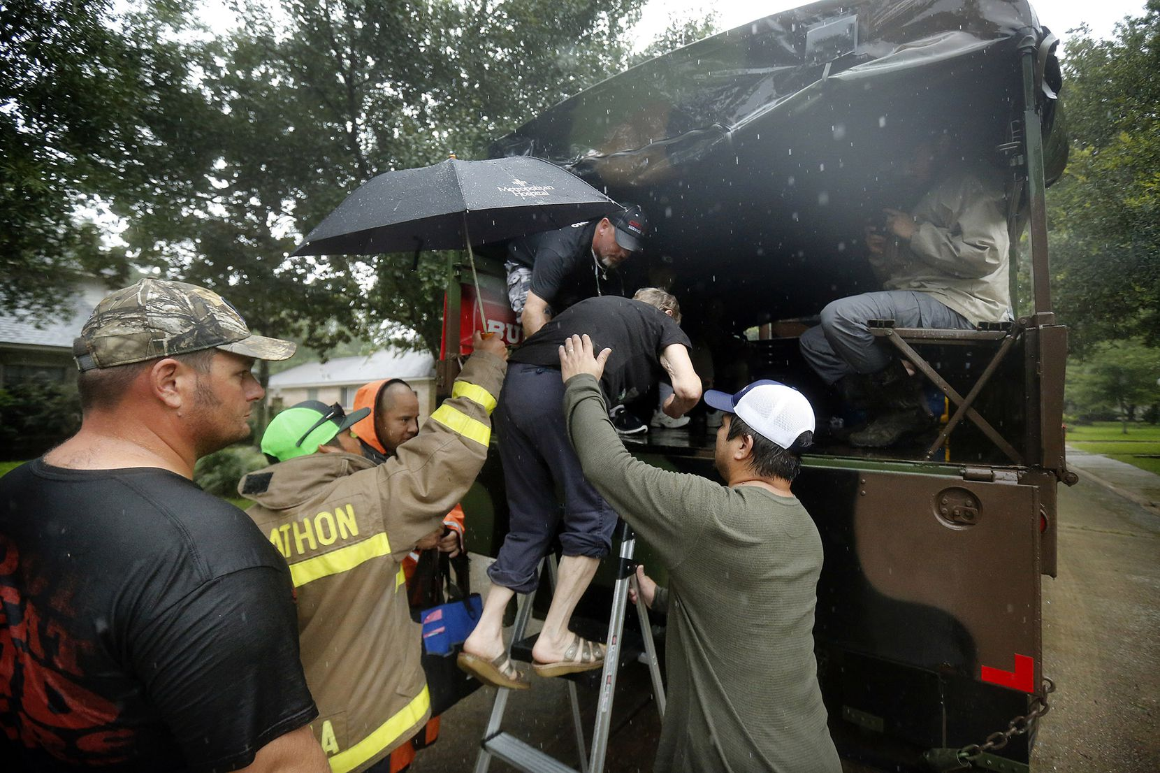 Volunteers help Carla Babinski into the back of a military-type transport truck as she took heed of a mandatory evacuation order to vacate their rain-soaked Dickinson, Texas home, Monday, August 28, 2017 in the wake of Hurricane Harvey. She and her husband and dog were part of the contingent that were moved.