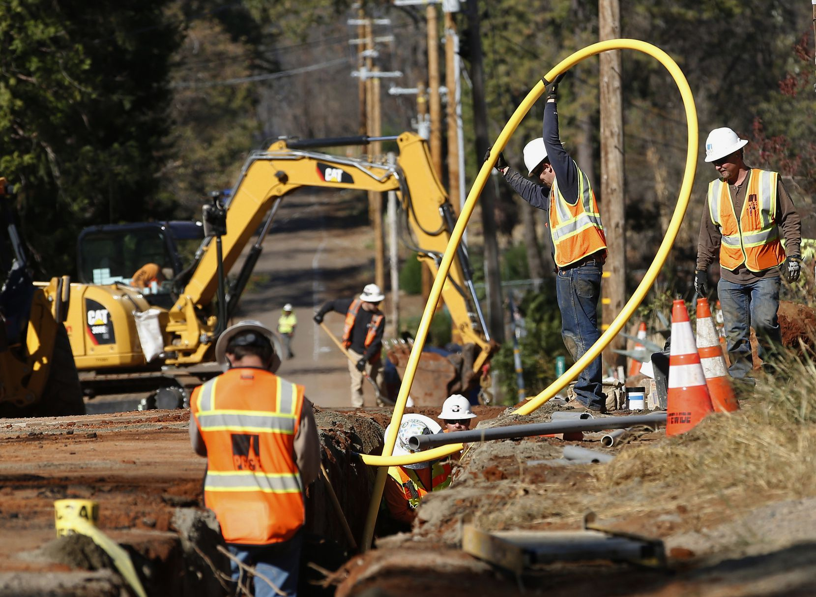 FILE - In this Oct. 18, 2019, file photo, Pacific Gas and Electric Company, workers bury utility lines in Paradise, Calif. A new technology being tested by California utilities, such as Pacific Gas & Electric Co. and Southern California Edison, is aimed at diagnosing problems before they could cause power outages or spark wildfires.