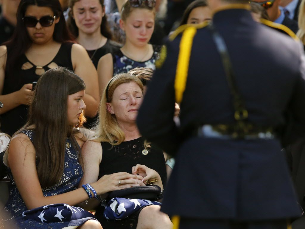Heidi Smith, wife of slain Dallas police Sgt. Michael Smith, is overcome with emotion as she is comforted by her daughter Victoria Smith (left) at the end of a graveside service at the Restland Funeral Home and Cemetery in Dallas, Thursday, July 14, 2016. Smith was gunned down in an ambush attack in downtown Dallas a week ago. Four Dallas police officers and one DART officer were killed. (Tom Fox/The Dallas Morning News)
