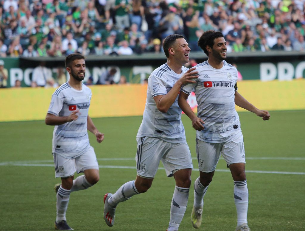 Los Angeles FC's Carlos Vela, right, smiles after a goal during an MLS soccer match against the Portland Timbers on Saturday, June 1, 2019, in Portland, Ore. (Tim Brown/The Oregonian via AP)