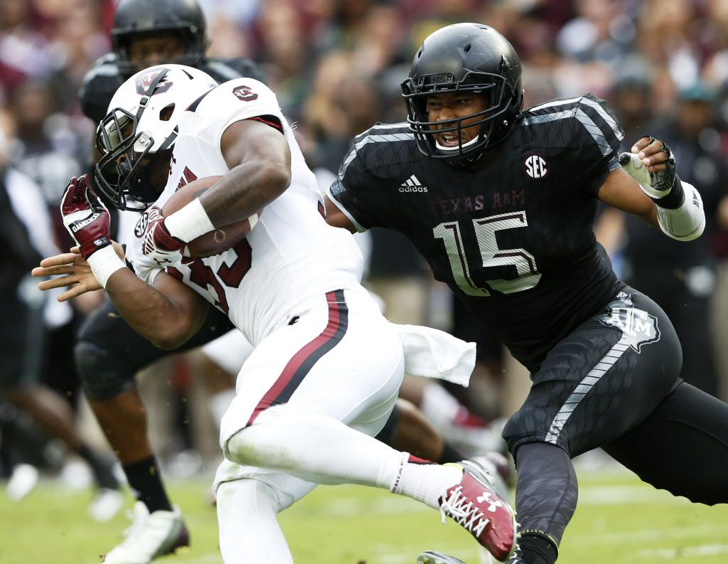 Texas A&M Aggies defensive lineman Myles Garrett (15) tackles South Carolina Gamecocks running back David Williams (33) during the first half of play at Kyle Field in College Station, on Saturday, October 31, 2015. (Vernon Bryant/The Dallas Morning News)
