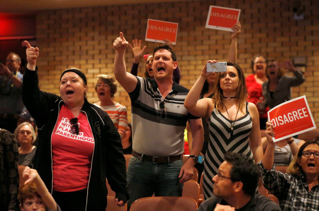 """People shout to """"vote him out"""" during a town hall meeting with Rep. Pete Sessions, R-Dallas, in the auditorium of Richardson High School on Saturday. (Vernon Bryant/The Dallas Morning News)"""