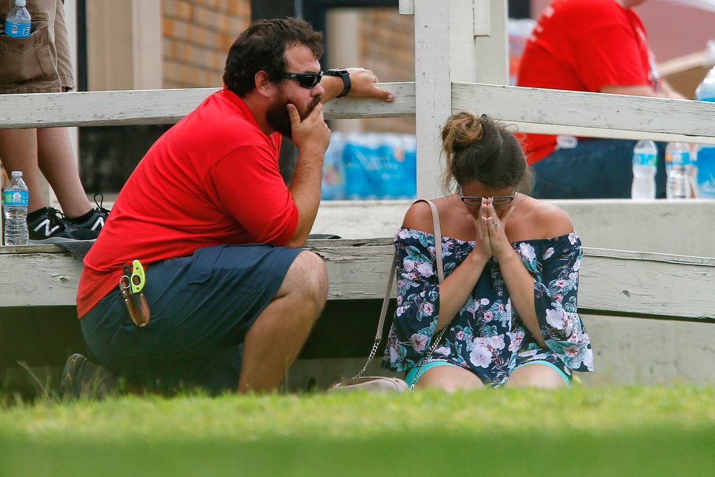 A woman prays in the grass outside the Alamo Gym where parents wait to reunite with their kids following a shooting at Santa Fe High School on May 18, 2018, in Santa Fe, TX. (Michael Ciaglo/Houston Chronicle)