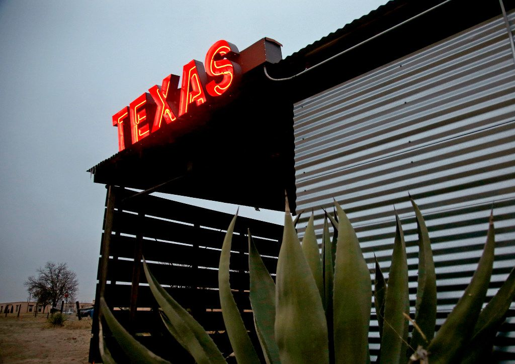 A neon sign marks the entry to the lobby at El Cosmico. (Guy Reynolds/Staff Photographer)
