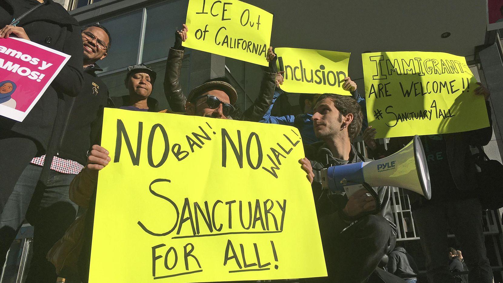 Un grupo de manifestantes mantiene carteles protestando por las restricciones a las ciudades santuarios y al muro fronterizo. (AP/Haven Daley)