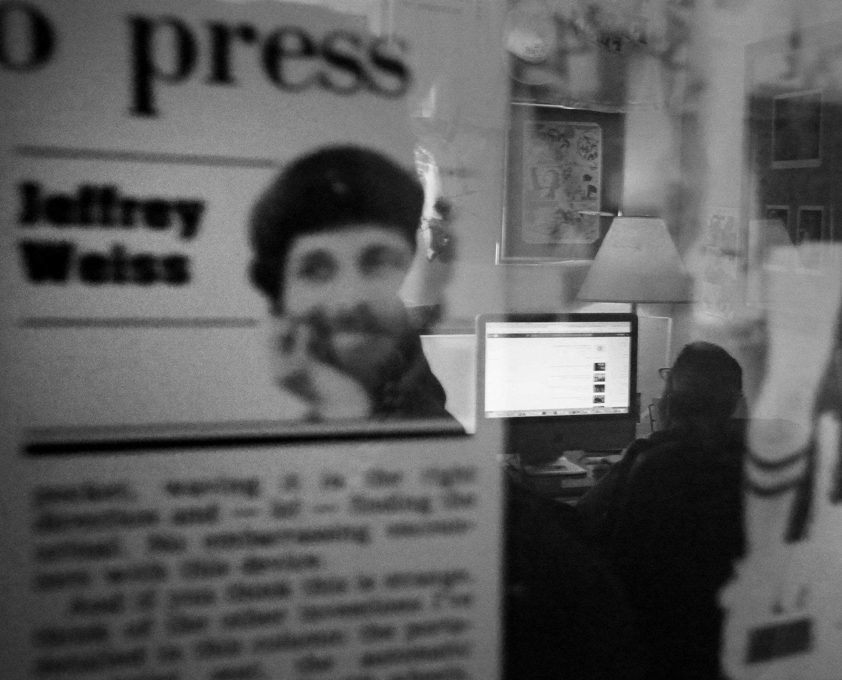 Weiss works in his office at his home in Dallas, as seen in a reflection of a framed press clipping on the wall. (Louis DeLuca/Staff Photographer)