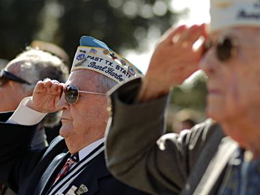 Pearl Harbor survivor Robert Tanner (second from left) saluted the flag during the Pledge of Allegiance.