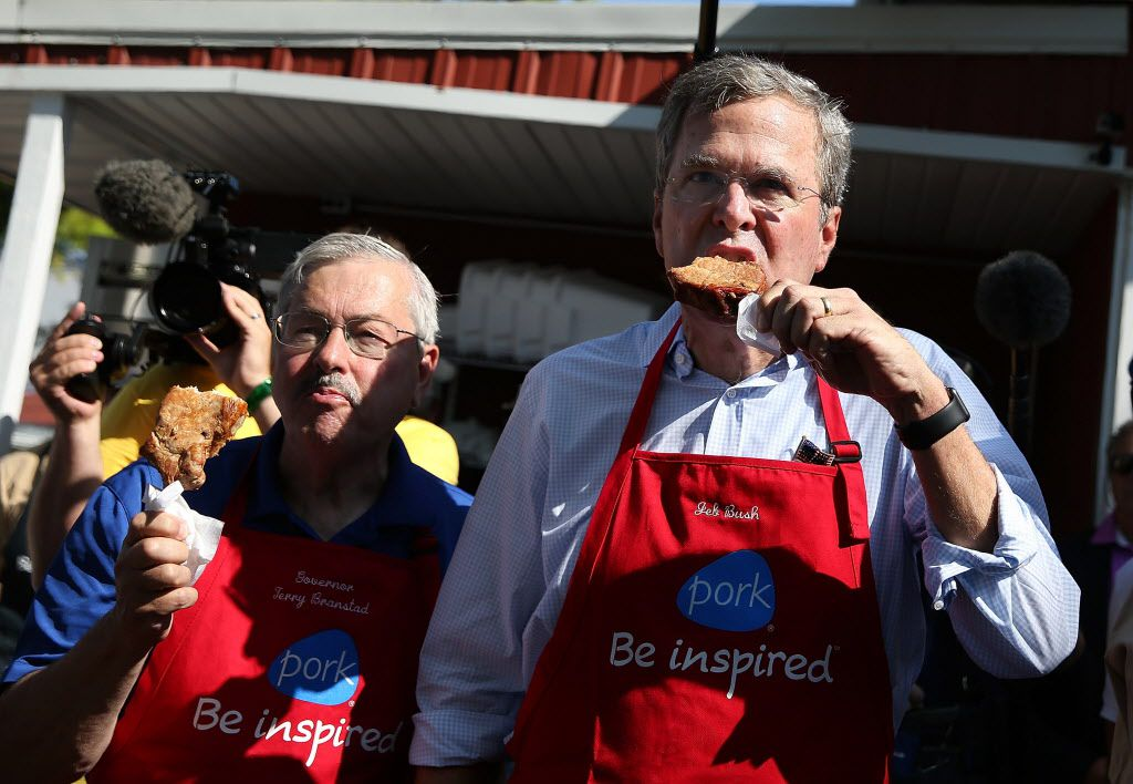 Republican presidential hopeful and former Florida Gov. Jeb Bush and Iowa Gov. Terry Branstad eat a pork chop on a stick at the Iowa Pork Tent during the Iowa State Fair.
