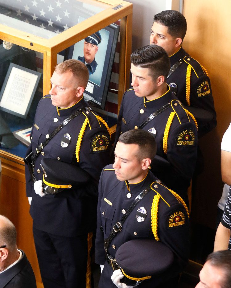 Dallas Police Officers stand at attention next to a display case honoring DART Police Officer Brent Thompson during the DART Police Department memorial service held in honor of National Police Memorial Week  at DART police headquarters on Thursday.