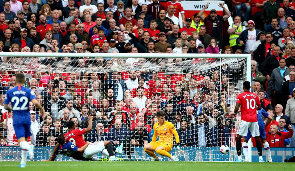 Manchester United's Anthony Martial, center left, scores his sides second goal past Chelsea's goalkeeper Kepa Arrizabalaga, center right, during the English Premier League soccer match between Manchester United and Chelsea at Old Trafford in Manchester, England, Sunday, Aug. 11, 2019. (AP Photo/Dave Thompson)