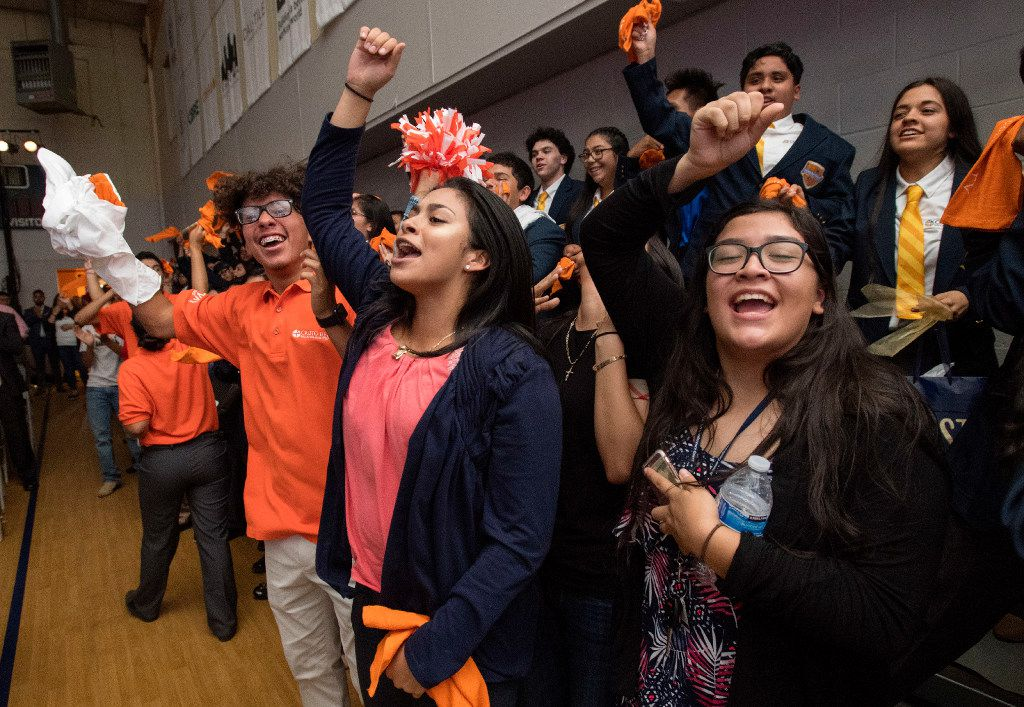 Cristo Rey Dallas College Prep upperclassmen Emily Casanova-Castillo, Eliazim Zamora, Alan Ruiz, right to left, cheer for the incoming freshmen who received their yearly work assignments with local corporations..