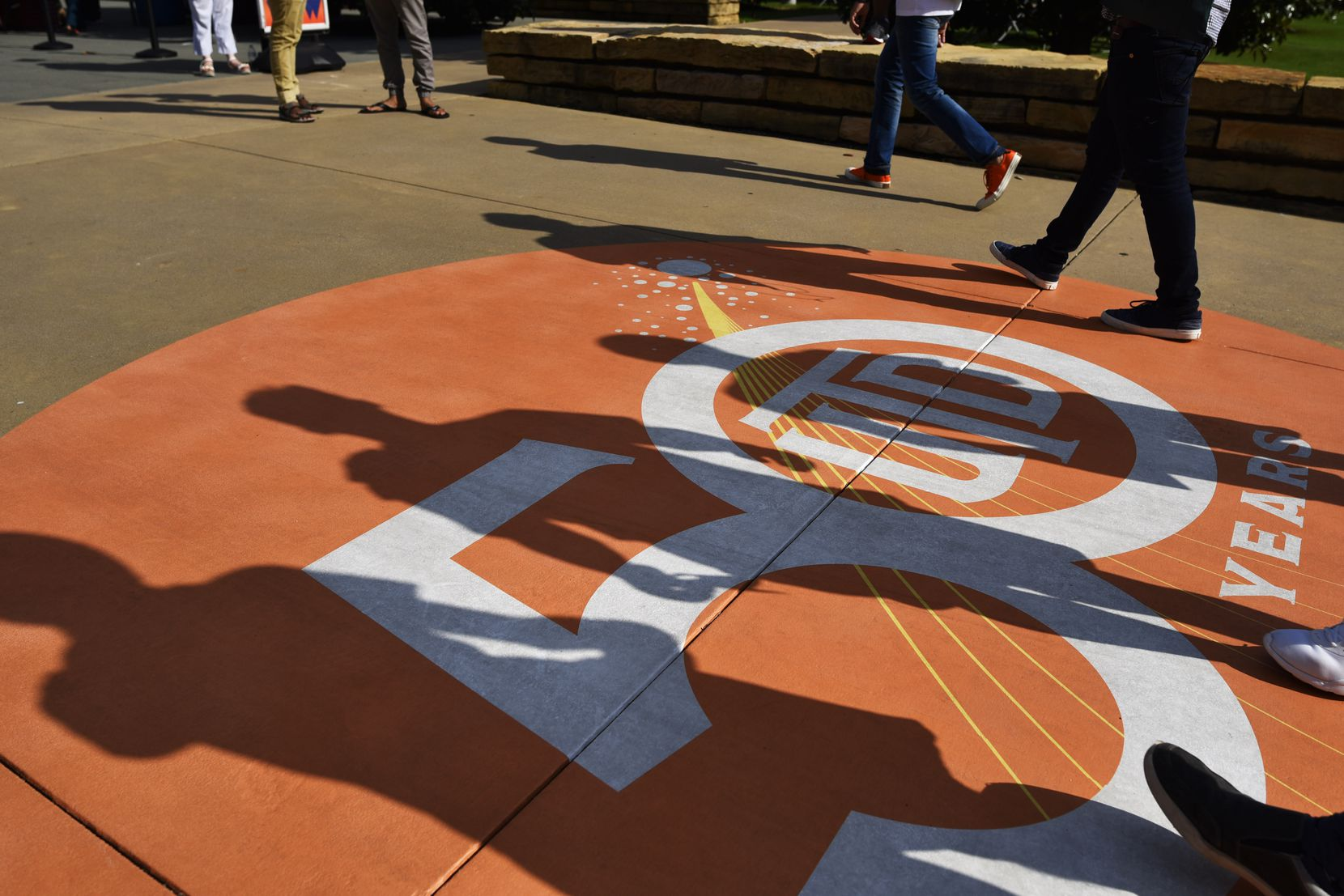 Shadows from freshman walk over a 50th anniversary logo celebrating 50 years of the University of Texas at Dallas, Sunday Aug. 18, 2019 in Richardson.