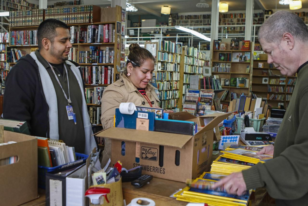 "Lucky Dog Books employee Mark Griffin rings up books and National Geographic magazines for customers Roy Gonzalez and Olivia Pintor. Sales picked up in the last two months, and the owner was encouraged by an uptick in ""younger faces."" But that hasn't been enough to keep the shop open."