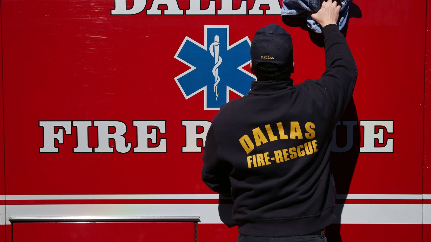 Firefighter John Smith cleans a vehicle outside Dallas Fire-Rescue Department fire station 44 at 2025 Lagow Street in Dallas in February 2016.