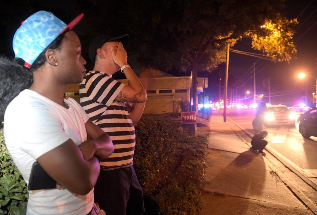 Jermainte Towns (izq.) y Brandon Shuford esperan por noticias luego de la balacera en el club Pulse de Orlando la madrugada del domingo. (AP/PHELAN M. EBENHACK)