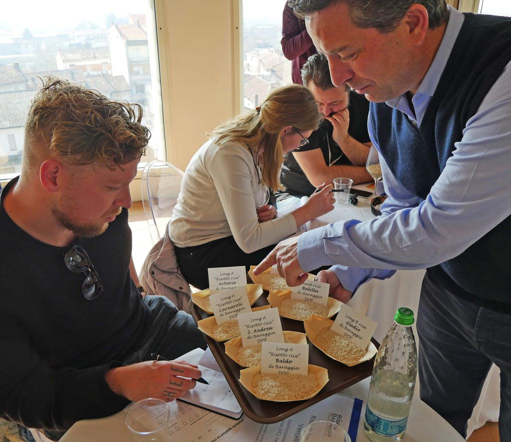 At a tasting of high-end rice in Piedmont, Italy, rice sommelier and agronomist Massimo Biloni points out nuanced differences among the grains to chef Bob Staal from Waterproef restaurant in the Netherlands.  What you may not be able to see: The fingers on Staal's right hand are tattooed with the letters: c-h-e-f.