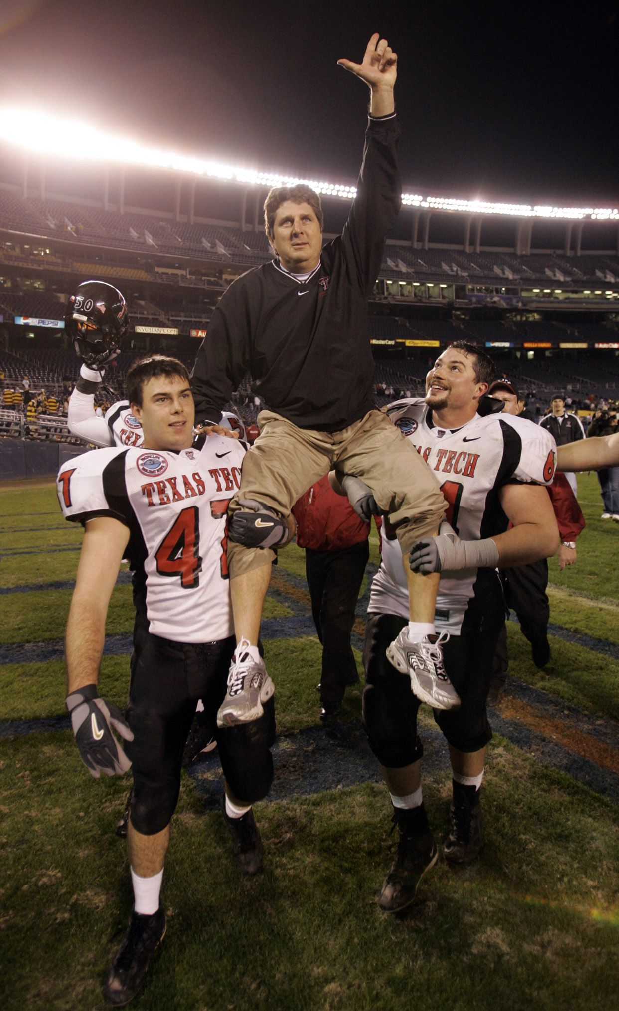 Texas Tech head coach Mike Leach is carried by Clay McGuire and Cody Campbell (right) after their victory against the University of California in the 2004 Holiday Bowl at San Diego's Qualcomm Stadium.