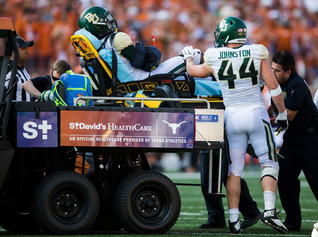 Baylor Bears linebacker Clay Johnston (44) pats defensive end Deonte Williams (40) on the knee as Williams is carted out of the game on a stretcher with his right arm in a cast during the third quarter of a college football game between Baylor and the University of Texas on Saturday, October 13, 2018 at Darrell K Royal Memorial Stadium in Austin, Texas.  (Ashley Landis/The Dallas Morning News)