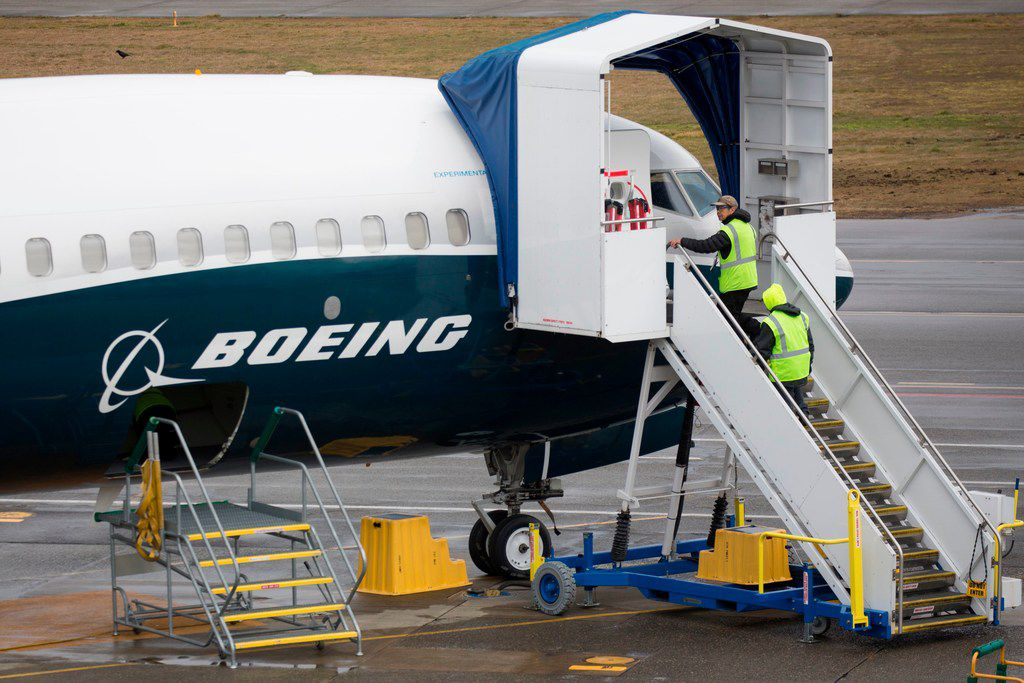 (FILES) In this file photo taken on March 12, 2019 workers are pictured next to a Boeing 737 MAX 9 airplane on the tarmac at the Boeing Renton Factory in Renton, Washington.