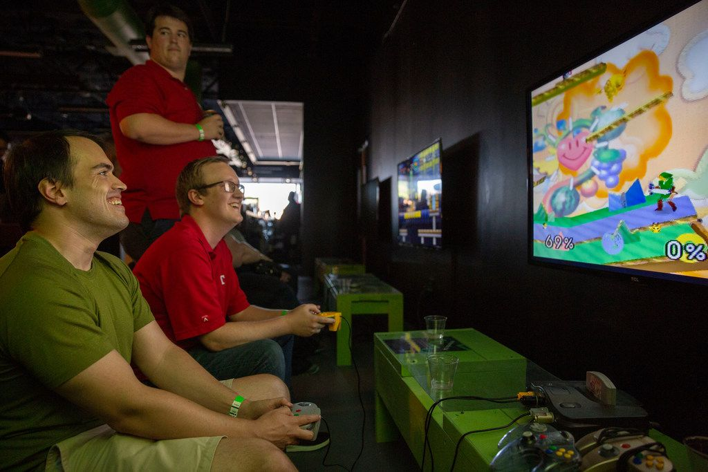 Friends Jon Goodwin (left) (CQ) and Shaun Hands (middle) play Super Smash Bros. on Nintendo 64 at the grand opening of Regeneration Arcade Bar and Pizzeria in Dallas.