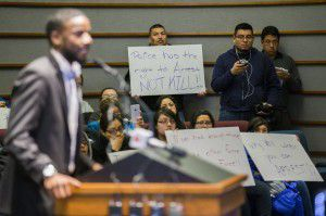 Protesters hold signs in support of Ruben Garcia Villalpando, who was fatally shot by a Grapevine police officer last month, on Tuesday, March 3, 2015 at Grapevine City Hall in Grapevine, Texas. Dominique Alexander, left, speaks to the city council in support of Garcia Villalpando. (Ashley Landis/The Dallas Morning News)