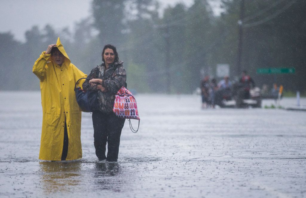 Rita Prosperie (left) and Connie McNeer walk out of floodwaters to safety near Highway 96 in Lumberton.