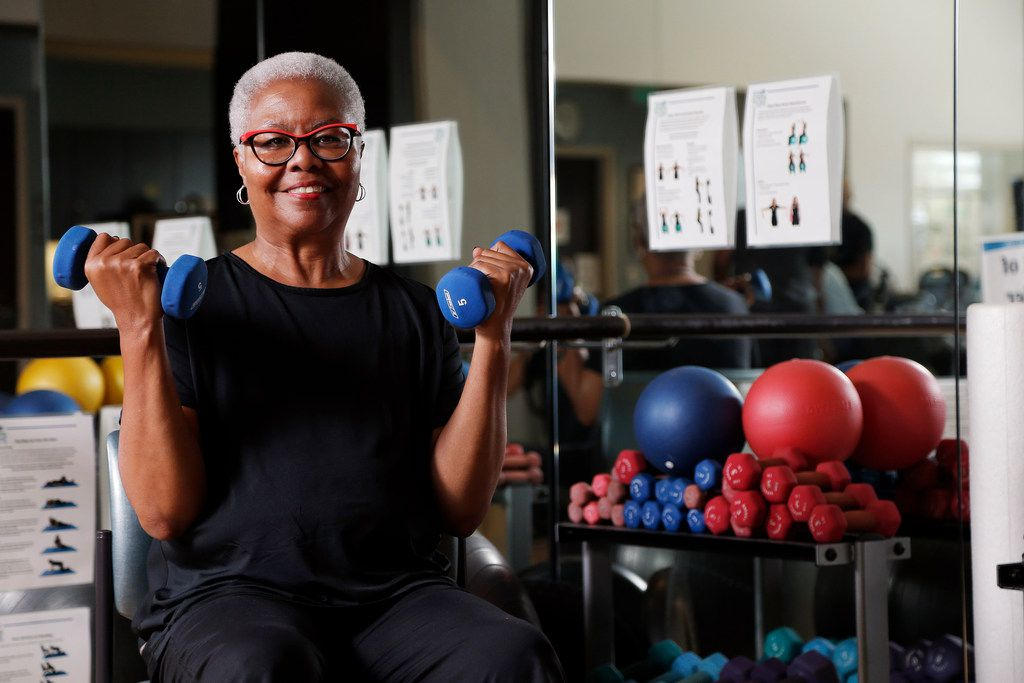 """Breast cancer survivor Dorothy Nelson poses for a photo with free weights that she uses to work out at the Baylor Sammons Cancer Center. Exercise she says, """"is now a major part of my life."""""""