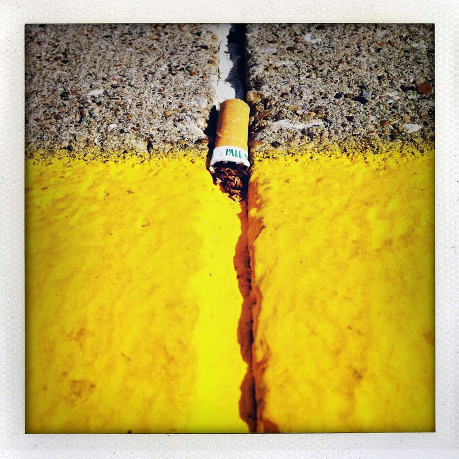 "A Pall Mall cigarette lies discarded in a street crack, part of a series of photographs jokingly titled ""Butt Cracks."""