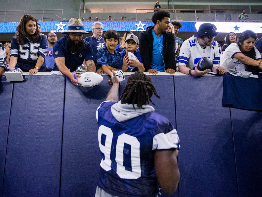 Dallas Cowboys defensive end Demarcus Lawrence (90) signs autographs for fans during a Dallas Cowboys training camp practice on Thursday, August 22, 2019 at The Star in Frisco.