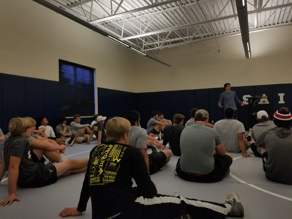 The Fort Worth All Saints football team participates in a weekly tradition of giving each other commitment cards. Players pictured here are in the back wrestling room as they share the commitment cards with each other on November 2, 2017. (Courtesy: Aaron Beck)