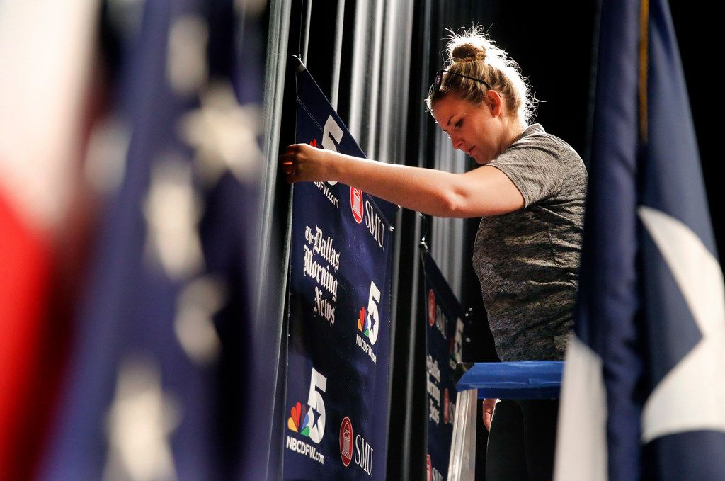 SMU technical director Faith Smith adjusts a banner as the stage is prepped for Friday's U.S. Senate debate on the campus of SMU in University Park, Texas, Thursday, September  20, 2018. KXAS and The Dallas Morning News are moderating the debate. (Tom Fox/The Dallas Morning News)